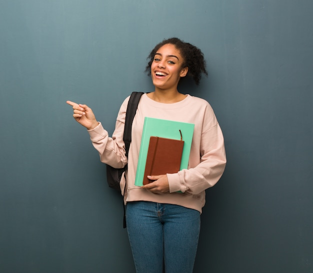 Jeune étudiante noire pointant sur le côté avec le doigt elle tient des livres