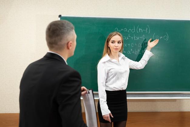 Jeune étudiante passe un examen près du tableau noir.