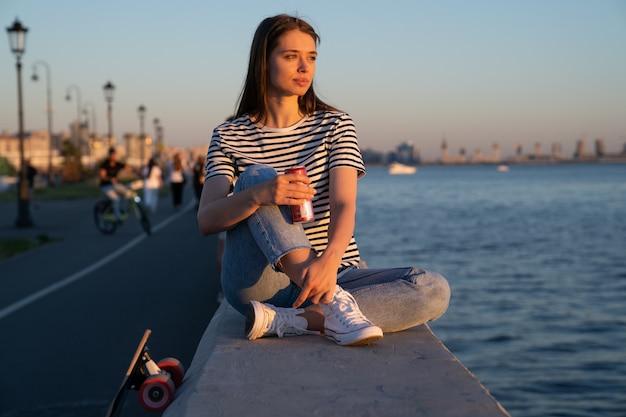 Jeune étudiante avec planche à roulettes et boisson se détendre en regardant le coucher du soleil au bord de la rivière et profiter de l'été