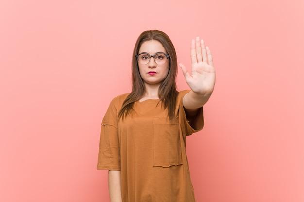 Jeune étudiante portant des lunettes debout avec la main tendue montrant le panneau d'arrêt, vous empêchant.