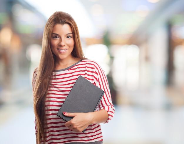 Jeune étudiante posant avec bloc-notes