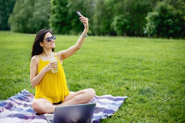 Jeune étudiante prenant un selfie sur smartphone assis sur l'herbe.