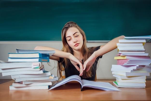 Jeune étudiante en préparation aux examens difficiles dans la salle d'étude, l'air fatigué et fatigué
