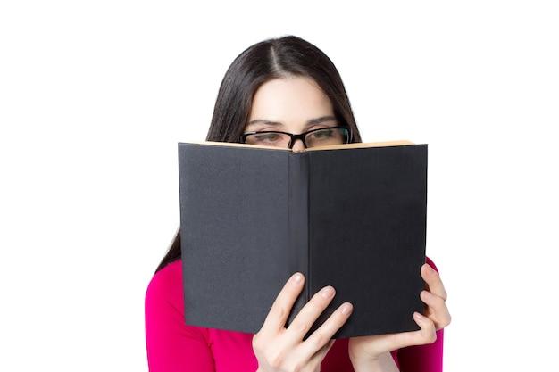Jeune étudiante professionnelle intelligente en chemise rouge et lunettes reding book, visage derrière le livre sur fond blanc, idée de concept de femme de connaissance
