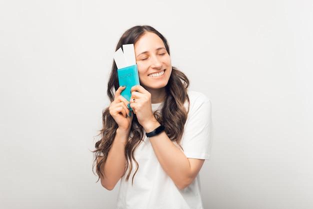Une jeune étudiante profite des billets qu'elle vient de recevoir, tout en tenant son passeport.