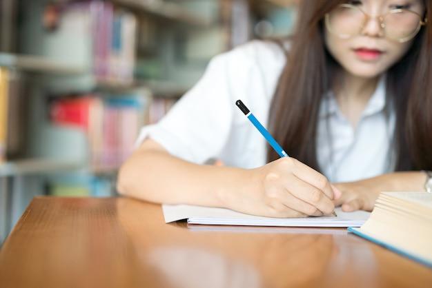 . jeune étudiante qui étudie dans la bibliothèque.