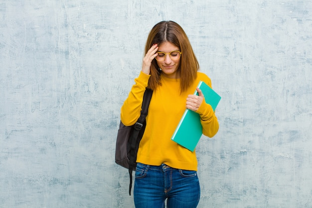 Jeune étudiante à la recherche concentrée, réfléchie et inspirée, brainstorming et imaginant avec les mains sur le front contre le mur grunge