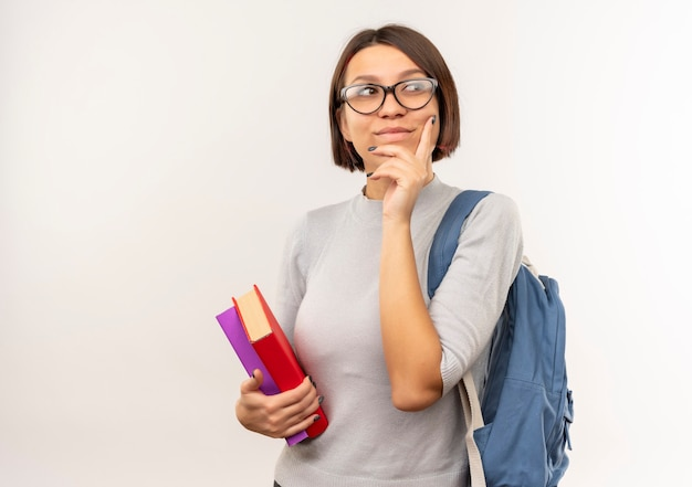 Jeune étudiante réfléchie portant des lunettes et sac à dos tenant des livres mettant la main sur le menton isolé sur un mur blanc