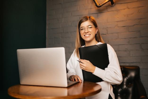 Jeune étudiante réussie sourit et s'assoit à une table en bois tenant un dossier avec des documents.