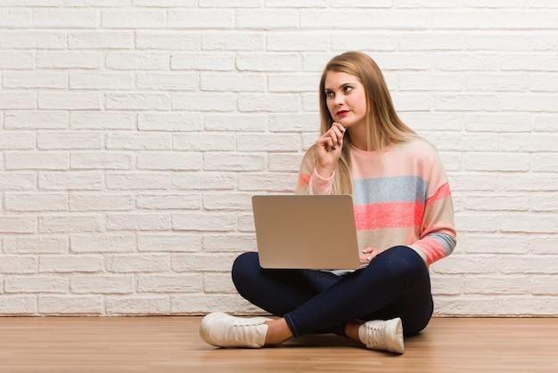 Jeune étudiante russe assise doutant et confus
