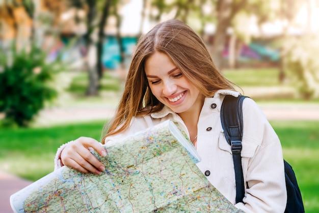 Une jeune étudiante se promène dans la ville avec une carte et cherche un moyen.