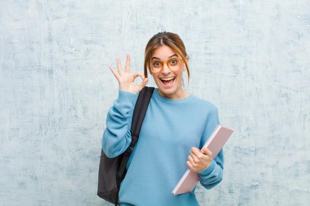 Jeune étudiante se sentant réussie et satisfaite, souriant avec la bouche grande ouverte, faisant signe avec la main