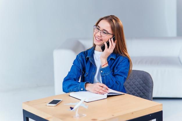 Jeune étudiante séduisante utilise un smartphone tout en étudiant à la maison.