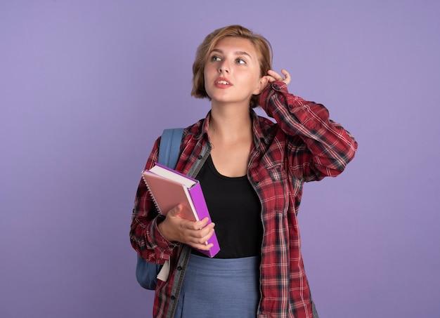 Une jeune étudiante slave confiante portant un sac à dos tient un livre et un cahier regarde de côté
