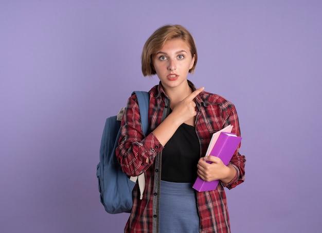Une jeune étudiante slave impressionnée portant un sac à dos tient un livre et un ordinateur portable sur le côté