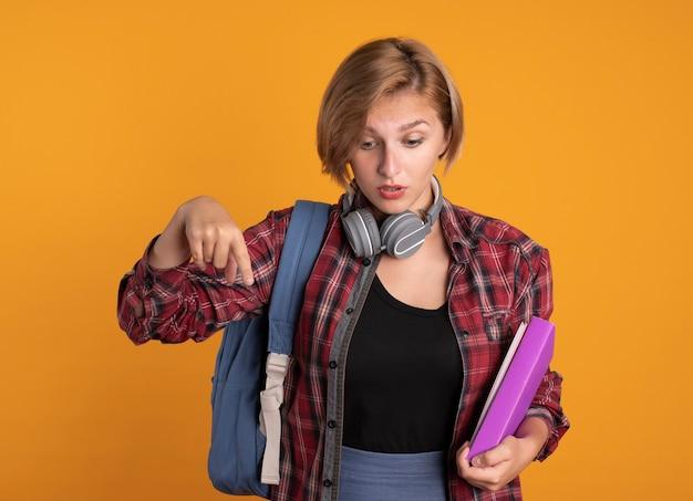 Une jeune étudiante slave surprise avec des écouteurs portant un sac à dos tient un livre et un cahier regardant et pointant vers le bas