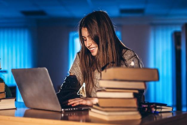 Jeune étudiante le soir est assise à une table dans la bibliothèque avec une pile de livres et travaille sur un ordinateur portable. se préparer à l'examen