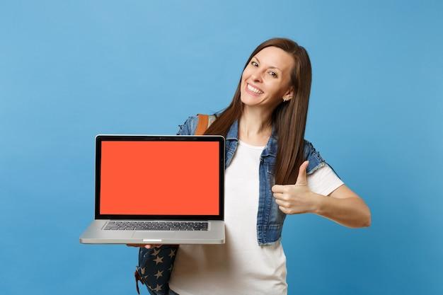 Jeune étudiante souriante avec sac à dos montrant le pouce vers le haut tenant un ordinateur portable avec un écran vide noir vide isolé sur fond bleu. l'éducation à l'université. copiez l'espace pour la publicité.