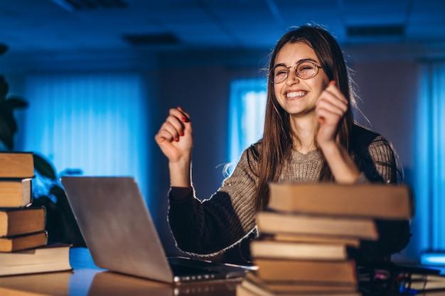 Jeune étudiante souriante le soir est assise à une table dans la bibliothèque avec une pile de livres et travaille sur un ordinateur portable. se préparer à l'examen