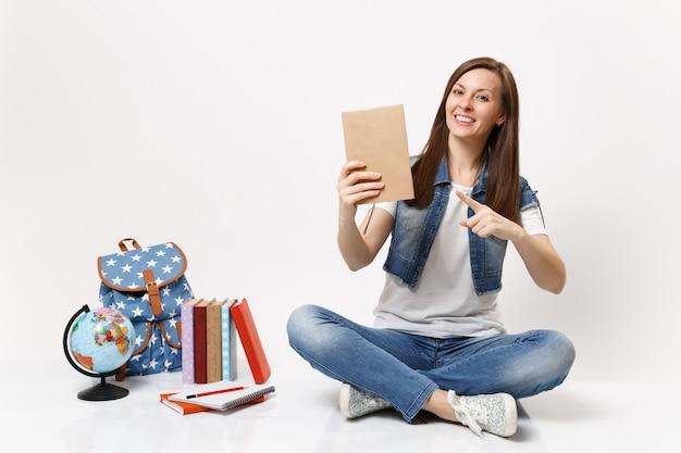 Jeune étudiante souriante en vêtements en denim pointant l'index sur un livre assis près du globe, sac à dos, livres scolaires isolés