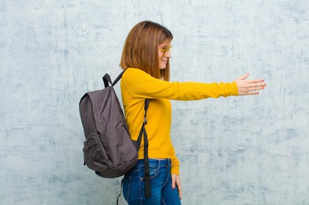Jeune étudiante souriante, vous saluant et vous offrant une poignée de main pour conclure un accord fructueux, concept de coopération sur fond de mur grunge