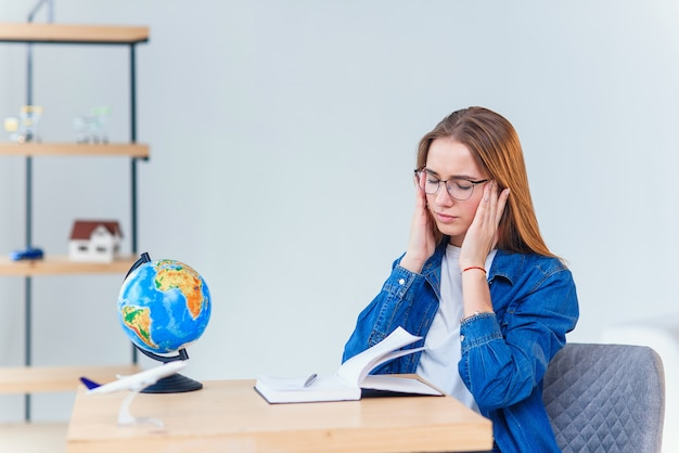 Une jeune étudiante stressante a des maux de tête après une dure journée d'étude. une femme surmenée a des maux de tête après une dure journée de travail, travaillant au bureau dans une armoire blanche.