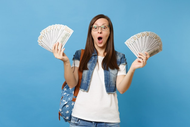 Jeune étudiante surprise choquée dans des verres avec sac à dos avec la bouche ouverte tenant beaucoup de dollars, argent comptant isolé sur fond bleu. éducation au collège universitaire secondaire.