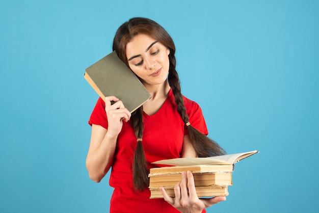 Jeune étudiante en t-shirt rouge lisant un nom de livre sur le mur bleu.
