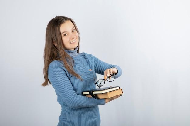 Jeune étudiante tenant des livres et des lunettes.