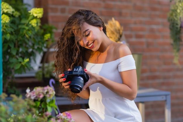 Jeune étudiante ou touriste séduisante utilisant un appareil photo sans miroir tout en marchant dans la ville d'été wo ...