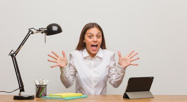 Jeune étudiante travaillant sur son bureau célébrant une victoire ou un succès