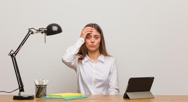 Jeune étudiante travaillant sur son bureau fatiguée et très fatiguée