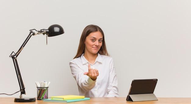 Jeune étudiante travaillant sur son bureau et invitant à venir