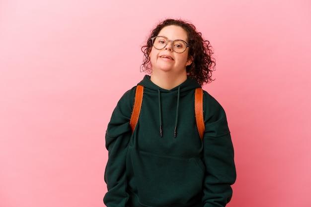 Jeune étudiante trisomique isolée sur fond rose heureuse, souriante et joyeuse.