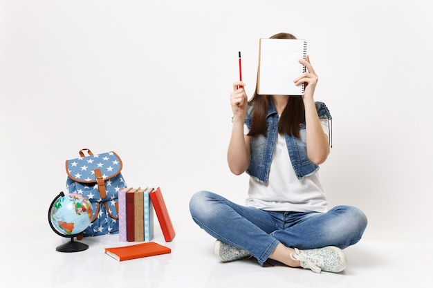 Jeune étudiante en vêtements en denim tenant un crayon couvrant le visage avec un ordinateur portable assis près du globe, sac à dos, livres scolaires isolés
