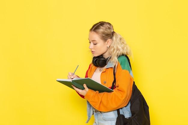 Jeune étudiante en vêtements modernes en écrivant des notes sur jaune