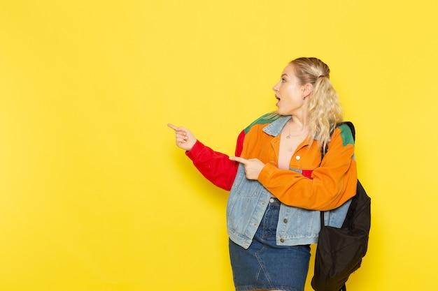 Jeune étudiante en vêtements modernes posant simplement avec le sourire sur le jaune