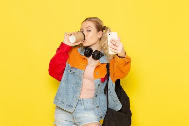 Jeune étudiante en vêtements modernes prenant un selfie avec du café sur jaune