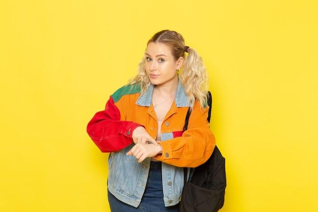 Jeune étudiante en vêtements modernes soulignant dans son poignet sur jaune