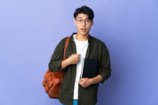 Jeune étudiante sur violet avec expression faciale surprise