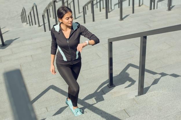 Jeune exercice d'exercice féminin dans la rue à l'extérieur en montant les escaliers