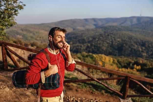 Jeune explorateur barbu debout dans la nature sur le soleil et mettre des écouteurs. l'homme passe belle journée d'automne ensoleillée dans la nature.
