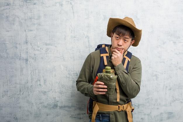 Jeune explorateur chinois doutant et confus