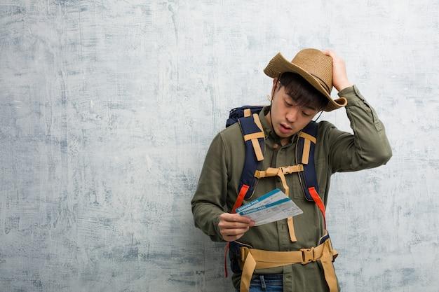 Jeune explorateur chinois tenant un billet d'avion inquiet et dépassé