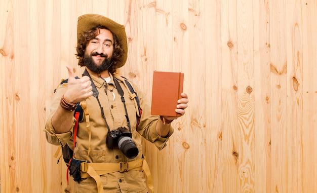 Jeune explorateur fou avec chapeau de paille et sac à dos sur fond de bois