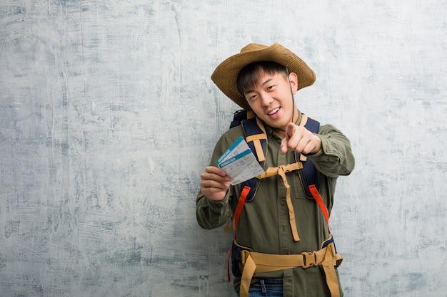 Jeune explorateur homme chinois tenant un billet d'avion gai et souriant pointant vers l'avant
