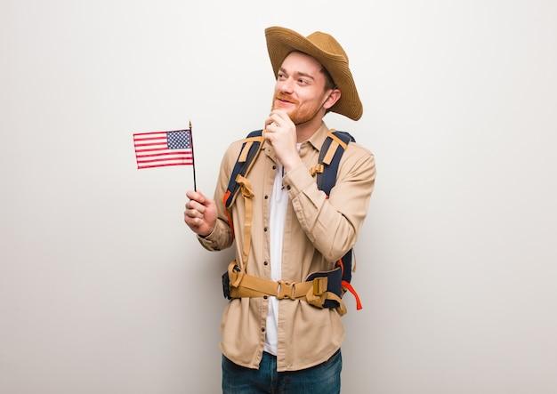 Jeune explorateur rousse doutant et confus. tenir un drapeau des états-unis.