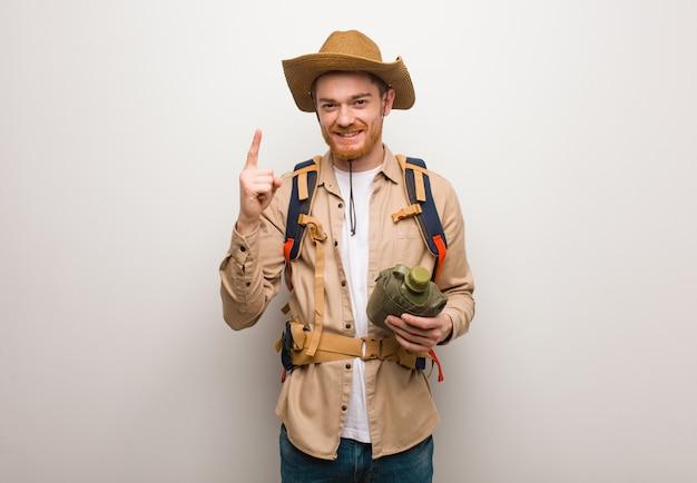 Jeune explorateur rousse montrant le numéro un. il tient une cantine.