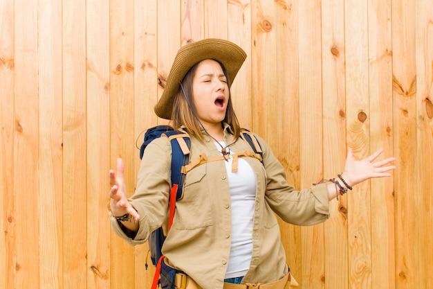 Jeune exploratrice latine femme contre bois