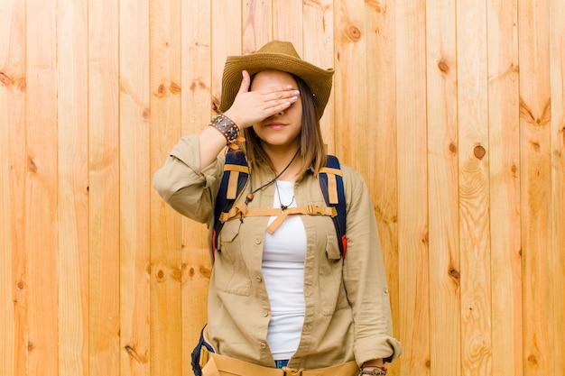 Jeune exploratrice latine femme contre mur en bois
